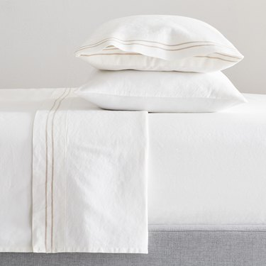 bed with white sheets with a small stripe