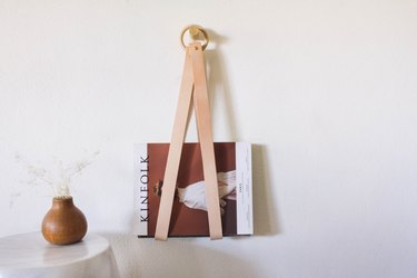 diy leather & wood magazine holder hanging on wall next to wood vase