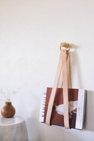diy leather & wood magazine holder hanging on wall next to wood vase