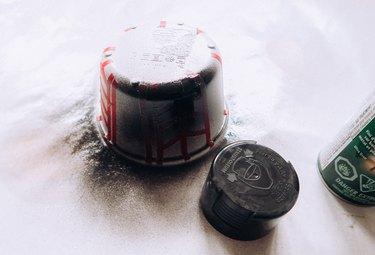 Spray painting jar with black paint