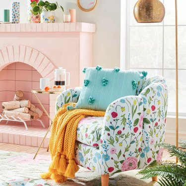 living room with light pink fireplace and floral armchair