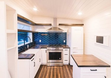 eco-friendly kitchen flooring with white cabinets and blue tile backsplash