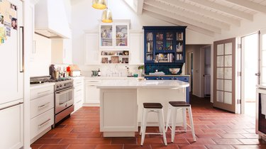 White kitchen island and white cabinetry on red-tile floor