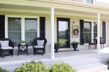 farmhouse style porch with black chairs and black window shutters