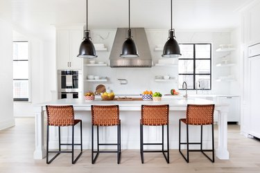 light wood kitchen floors in white space with black accents by Chango & Co.