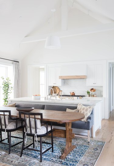 wood trestle table with gray kitchen island with bench seating