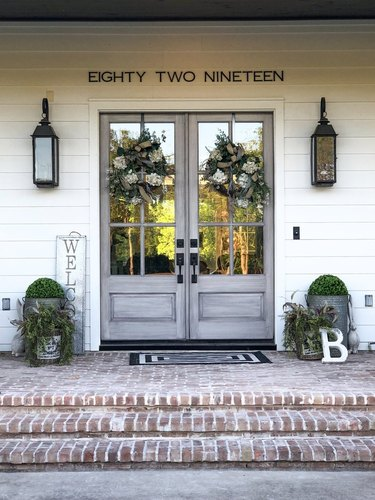 farmhouse style exterior with brick steps and gray glass doors