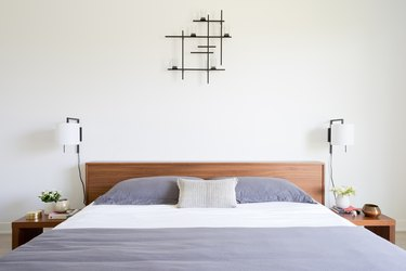 modern bedroom with wall sconces on either side of wood headboard