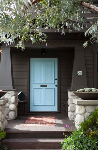 blue Craftsman-style door paired with dark brown siding