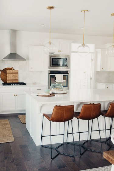 Dark wood kitchen flooring idea with leather bar stools and globe pendant lights