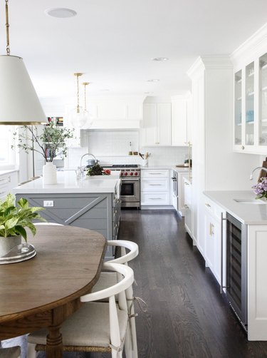 Dark wood kitchen flooring idea with white cabinets and white walls