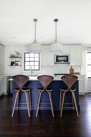 Dark wood kitchen flooring idea with blue island and modern pendant lights