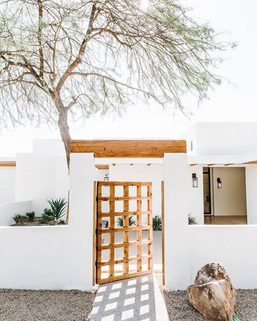 Desert style home with white exterior and reclaimed wood gate