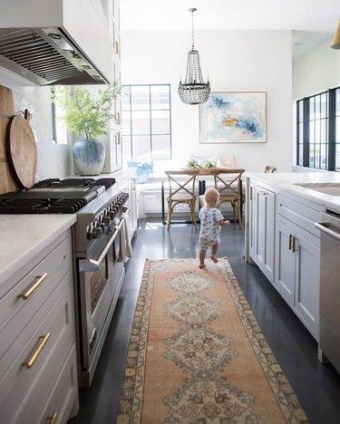 white kitchen dark floors with brass hardware and dark concrete floors with kitchen runner