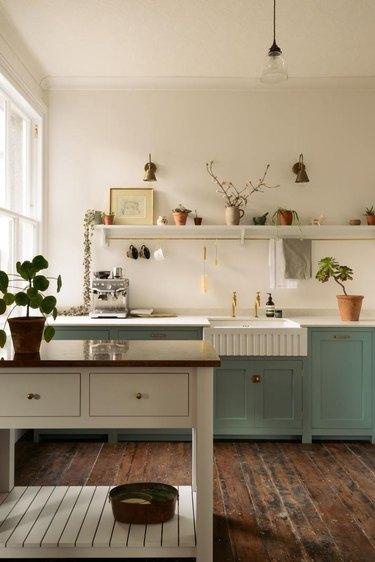 Dark wood kitchen flooring idea with reclaimed wood floor and green cabinets