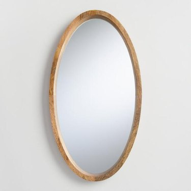 Oval mirror with wooden border in medium finish