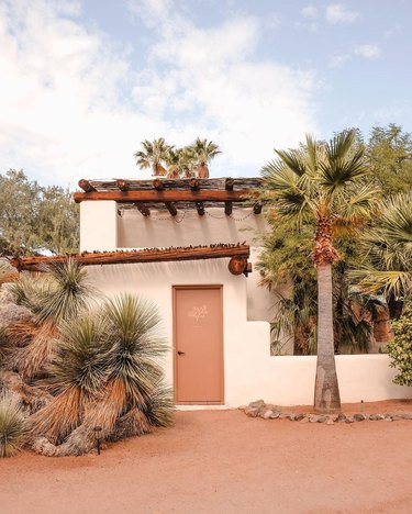 Desert style home in the adobe style with palm trees and exposed timbers