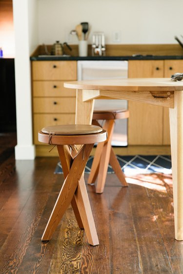 Dark wood kitchen flooring idea with wood stools, table, and cabinets
