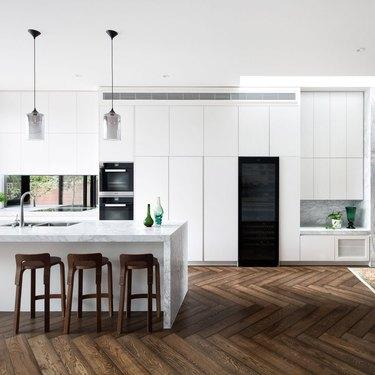 Dark wood kitchen flooring idea in a herringbone pattern and white cabinets