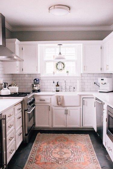 white kitchen dark floors with hexagon floors and kitchen rug