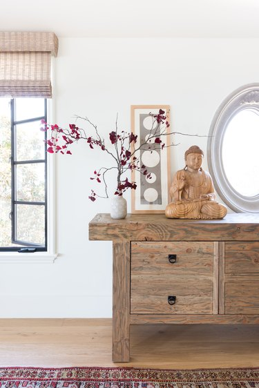 A vintage butcher's table with buddha sculpture and flowers