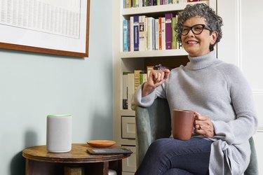 woman sitting with mug near Amazon Echo