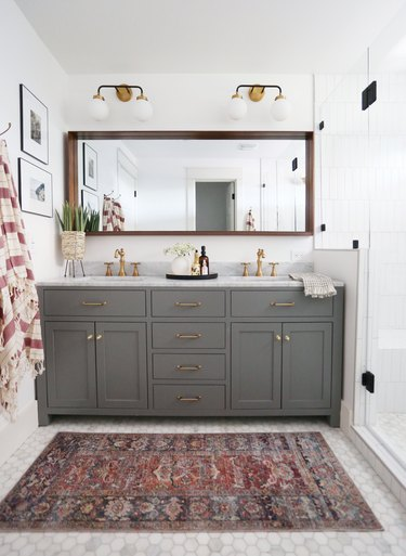 Double bathroom vanity with gray cabinets and wall sconces