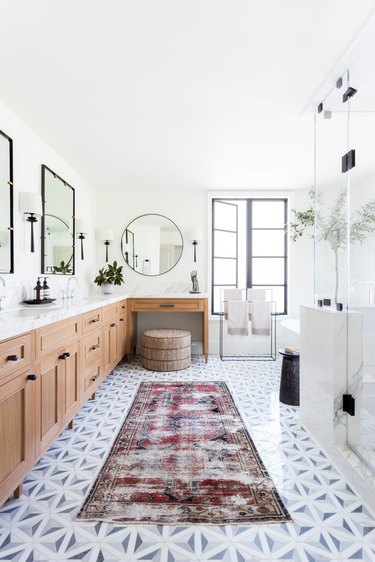 The huge master bath with mosaic tile and vintage rugs