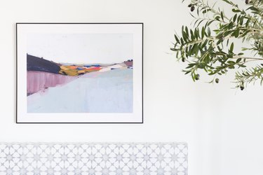 Abstract painting above a stone fireplace