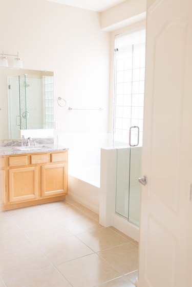 Painted bathroom cabinets before and after featuring light wood cabinets and beige floor tile