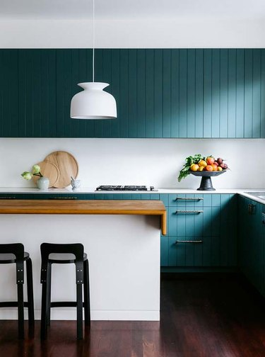 minimalist kitchen with green beadboard cabinets