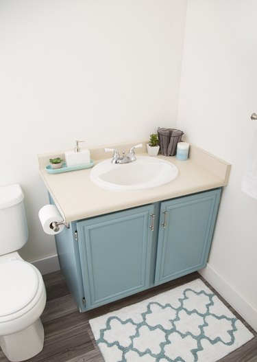 Painted bathroom cabinets before and after featuring light blue cabinets