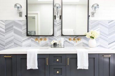 Double bathroom vanity with patterned backsplash and gray cabinets