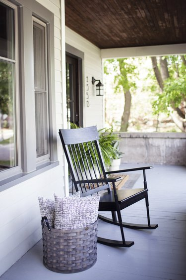 Craftsman front porch with black rocking chair and basket with pillows