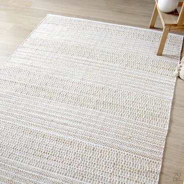White and cream Scandinavian rug with subtle pattern on floor