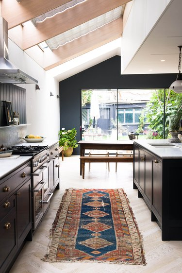vintage navy and orange rug for kitchen floor with black cabinets