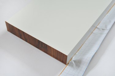 corner of white shelf covered in dark brown contact paper