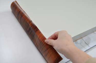 hand folding brown contact paper over shelf edges