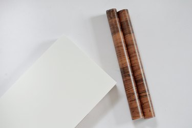 white ikea shelf and roll of walnut contact paper