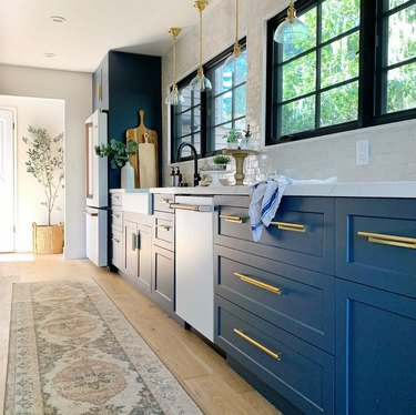 rug for kitchen floor with navy and brass cabinets in eclectic kitchen