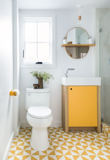 yellow patterned tiling and yellow fixtures in white bathroom
