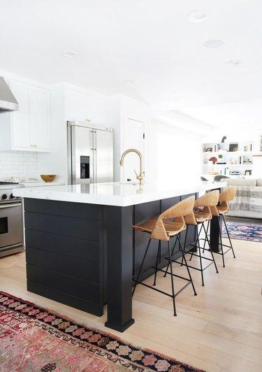 white kitchen with dark island and rattan chairs
