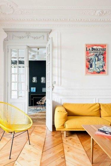 Paris apartment with herringbone wood floors and yellow sofa