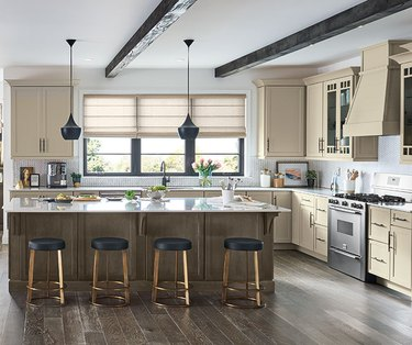 Cream kitchen with contrasting wood floor and island, plus barstool seating.