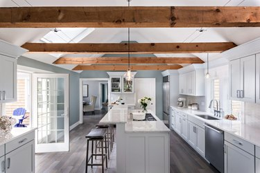 wooden gray kitchen island with additional ledge and reclaimed wood ceiling beams