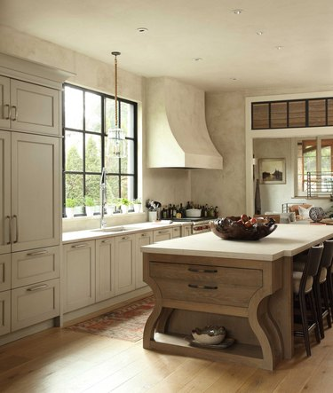 Inviting cream kitchen with custom island with seating and storage with wood floors below.