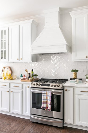Shiny white herringbone backsplash with white cabinets and cooking tools