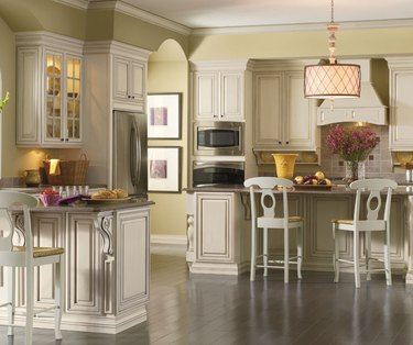French country–themed kitchen with cream, decorative cabinetry.