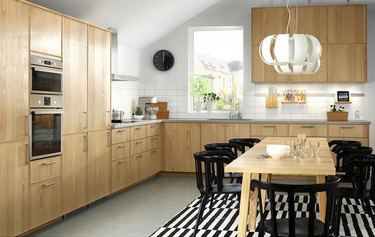 IKEA black and white rug for kitchen floor with wood cabinets