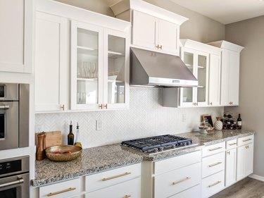 White herringbone backsplash in small tiles with white cabinets